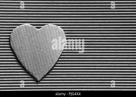 Valentine - heart symbol carved out of corrugated cardboard. Copy space. Free space for text, Close-up, top view. Black and white photo - Stock Photo