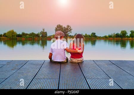 Boy with flat cap and little girl are sitting on pier. Boy is giving a hug his little sister.  Love, friendship and childhood concept. Beautiful romantic sunset picture - Stock Photo
