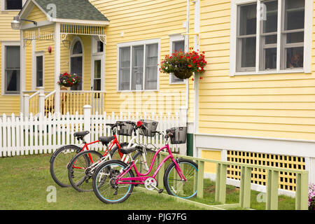 Bicycles parked in front of a charming yellow home, are the main form of transportation on Mackinac Island. This is a popular vacation spot in Michigan. - Stock Photo