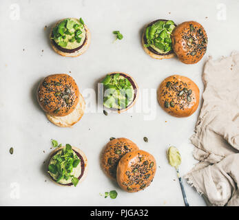 Flat-lay of healthy vegan burgers with quinoa beetroot patties, avocado cream and green sprouts over light background, top view . Vegetarian, clean ea - Stock Photo
