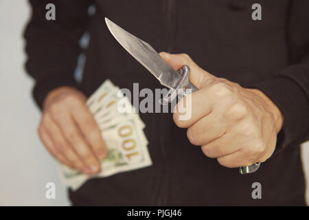 Robber with knife in hand and American money. bandit pulls out his pocket folding knife to threats. a robber with a knife in the hoodie. The concept o - Stock Photo