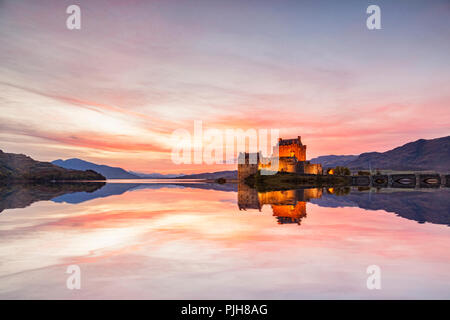 Eilean Donan Castle illuminated at twilight, Highland, Scotland, UK, reflected in the waters of Loch Duich. - Stock Photo