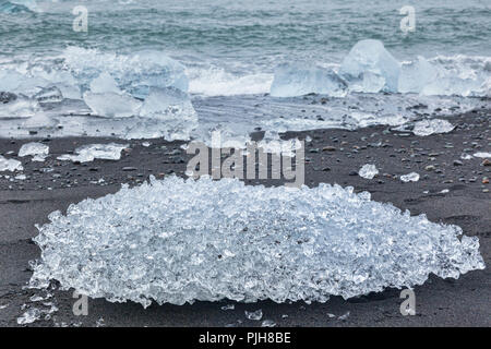 Ice on Diamond Beach, South Iceland, where ice from Jokulsarlon Glacial Lagoon is deposited on the volcanic black sand. - Stock Photo