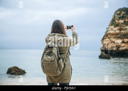 Girl tourist with a backpack photographing a beautiful landscape standing on the Atlantic coast. - Stock Photo