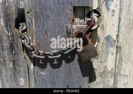 Old Yale lock and chain on a paint flaked garage door - Stock Photo