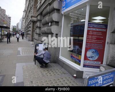Assistant marks up exchange rates on board at Thomas Exchange Global Limited, Bureau de Change, Currency Exchange, London, UK - Stock Photo