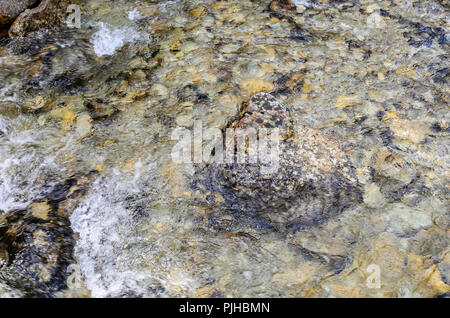 Mountain river. The texture of the rocky bottom is visible. - Stock Photo