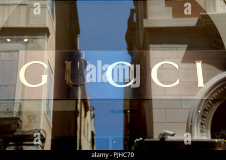 VENICE, ITALY - JUNE 18, 2018: striking Gucci signage in Venice main street with buildings reflections - Stock Photo