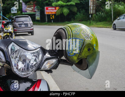 Pahang, Malaysia - Jun 22, 2014. Hanging helmet on scooter in Cameron Highlands. Cameron is the most popular of the highland retreats in Malaysia. - Stock Photo