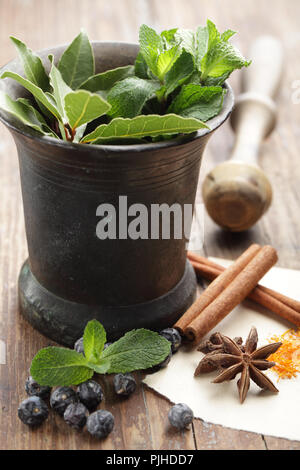 Spices on the rustic table and in the vintage mortar - Stock Photo