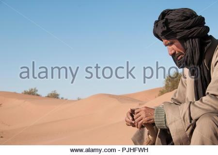 Morocco, Western Sahara, camel driver in the sand desert - Stock Photo