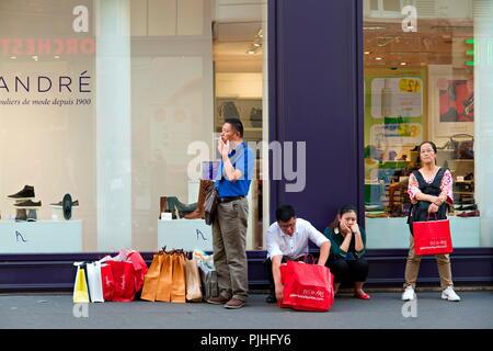 France, Paris, 9th arrondissement, rue de la Chaussee d'Antin, Chinese tourists waiting across the stree of Galeries Lafayette department store - Stock Photo