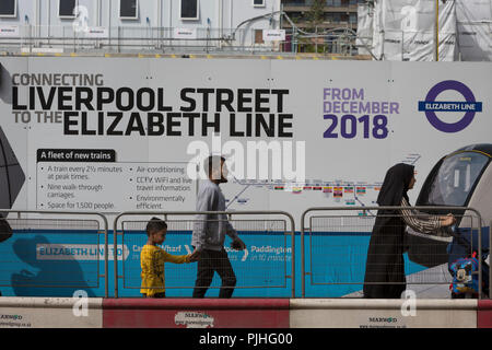 Londoners and commuters walk past the billboards promoting Crossrail's new Queen Elizabeth rail line, the capital's newest  on 3rd September 2018, on Moorgate in London, England. Crossrail's Elizabeth Line is a 118-kilometre (73-mile) railway line under development in London and the home counties of Berkshire, Buckinghamshire and Essex, England. Crossrail is the biggest construction project in Europe and is one of the largest single infrastructure investments ever undertaken in the UK - a£15bn transport project that was due to open in December 2018 but now delayed to autumn 2019. - Stock Photo