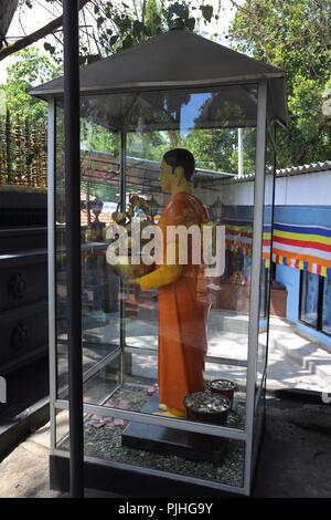 Galle Sri Lanka Rumassala Road Sri Vivekaramaya Temple Standing Buddha with Money around his feet as offerings - Stock Photo