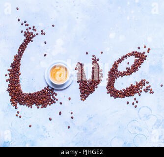 White Cup Fresh Coffee Text Love with Scattered Grains Unhealthy Food Top View Blue Background Concept of Valentines Day - Stock Photo