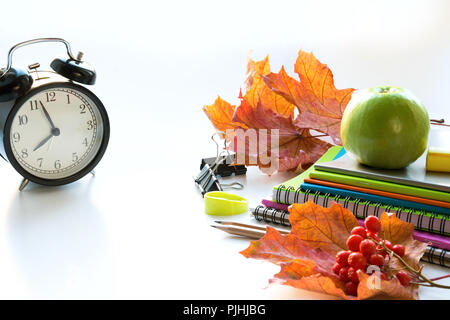 Colorful school supplies, book, and alarm clock on white. Top view, flat lay. Top view, copy space. Back to school. - Stock Photo