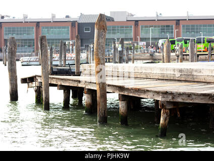 wooden pier supported in piles to embark tourist in Venice, in the background three green buses with a group of people and boats - Stock Photo