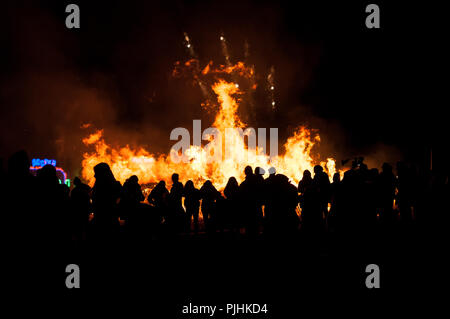 People are silhouetted against the flames of a large bonfire on the 5th of November, Guy Fawkes Night, Bonfire Night. - Stock Photo