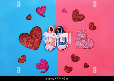 Baby sneakers on pink and blue background - Stock Photo
