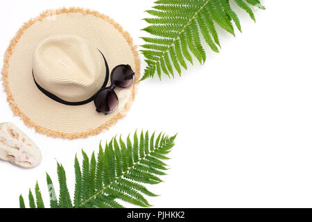 Tropical vacation. Straw beach sunhat, sun glasses, leaf of fern on white. Top view with copy space. Summer concept. - Stock Photo