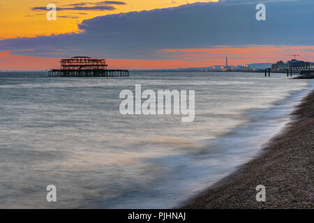 The beach in Brighton, England, after sunset with the ruin of the old pier in the back - Stock Photo