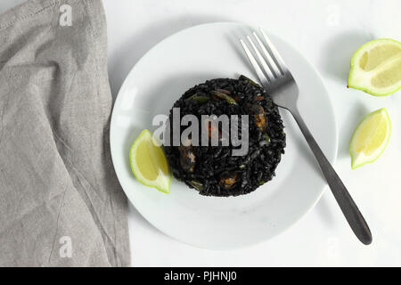 Traditional arroz negro - arròs negre - black rice dish, typical for Valencia, on white marble surface - Stock Photo