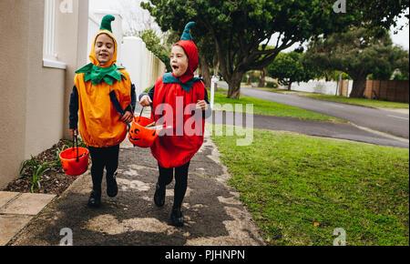 Identical twin sisters in halloween costume with halloween bucket walking on sidewalk. Halloween kids trick or treating. - Stock Photo