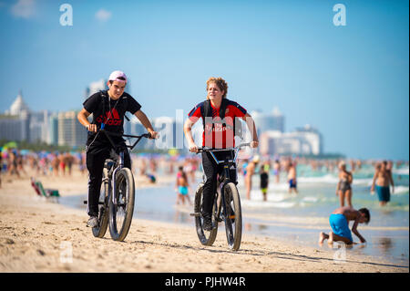 MIAMI - CIRCA AUGUST, 2018: Two young men cycle along the shore South Beach on a hot summer weekend. - Stock Photo
