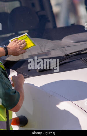 traffic warden civil enforcement officer wearing reflective yellow vest issuing fixed penalty parking ticket fine to white van - Stock Photo