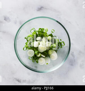 chopped green onions in a glass bowl on a marble table - Stock Photo
