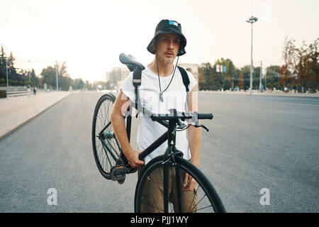 Portrait of a blonde white man in the city with a classic bike on shoulder, looking to camera while standing on a road in the city - Stock Photo