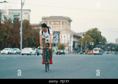 Portrait of a young man riding on bicycle in the city road, street with city far in the background. Male on black bicycle with white shirt, cap, backp - Stock Photo