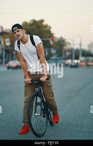 Stylish Man With Bicycle Going To Work On Street. Portrait Of Young Male In Casual Clothes With Backpack Walking On City Street With Stylish Bike. Red - Stock Photo