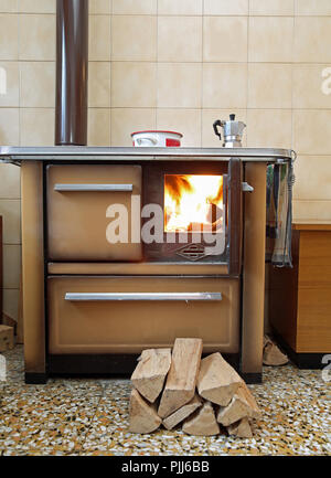 stove lit in a mountain cabin with a moka pot on top - Stock Photo