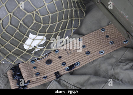 ww2 us army pistol belt and helmet with ace of spades emblem on green uniform background - Stock Photo