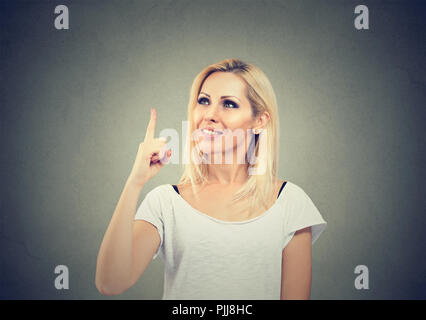 Portrait of a casual woman holding finger up having bright idea on gray background - Stock Photo