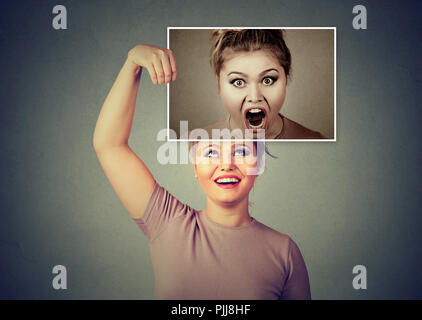 Young woman smiling while holding picture of herself in angry mood and screaming having split personality - Stock Photo