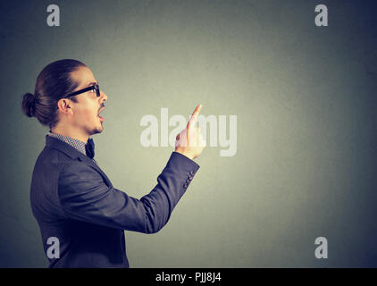 Side view of business man in holding finger up having bright idea on gray background - Stock Photo