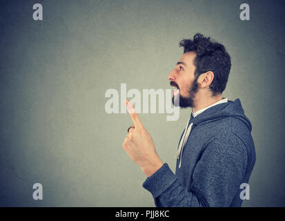 Side view of casual man in hoodie holding finger up having bright idea on gray background - Stock Photo