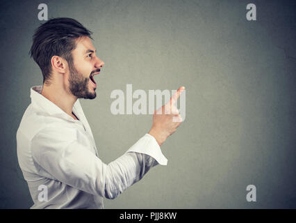 Side view of casual man in white shirt holding finger up having bright idea on gray background - Stock Photo