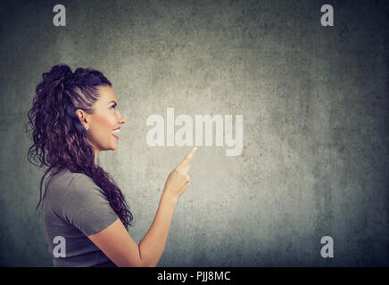 Side view of excited woman holding finger up having bright idea on gray background - Stock Photo