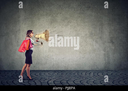 Sale concept, stylish young woman shopper shouting in megaphone walking on a street - Stock Photo