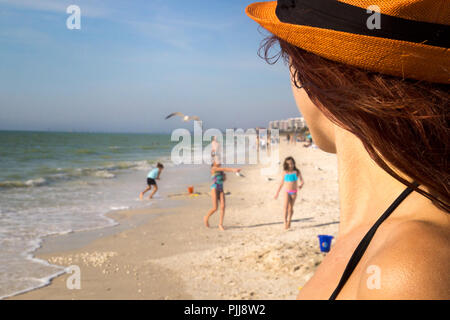 Family holiday, woman detail watching children playing on beautiful sea beach in Florida, Barefoot Beach County Preserve, Naples, Bonita Springs USA - Stock Photo