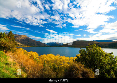 Autumn landscape colourful scenery with trees, lake and golden hills of Central Otago region, Lake Hayes, village Arrowtown, road trip from Queenstown - Stock Photo
