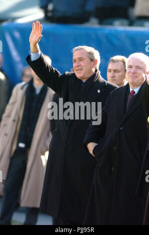 U.S. President George W. Bush waves to spectators as Senator John McCain, right, looks on during opening ceremony for the 105th Army vs. Navy football game December 4, 2004 in Philadelphia, Pennsylvania. - Stock Photo