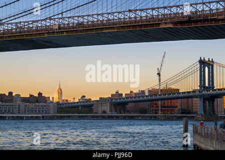 New York city bridges, Manhattan bridge view and Brooklyn bridge in front, Empire State Building in distance, sunset light, NY USA - Stock Photo