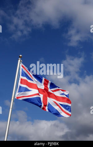 Union Jack Flag flying in the wind on a sunny day in England - Stock Photo