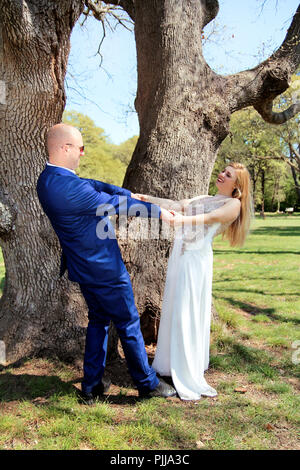 Wedding. Happy wedding couple in the forest. Happy married couple is standing and hands wide open. A wedding couple who stay and enjoy in the natural. - Stock Photo