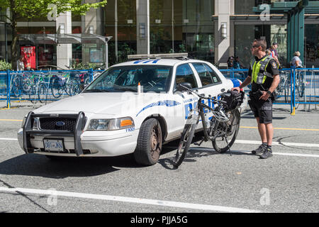 Vancouver City Policeman with bike, and vehicle blocking the street during an event, Vancouver city. - Stock Photo