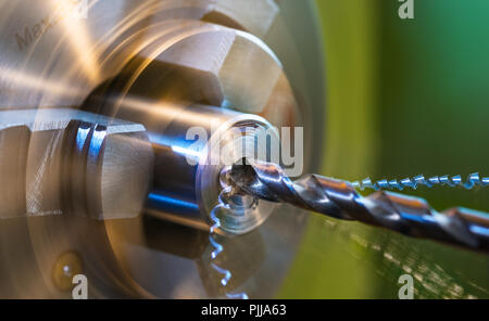Drilling on lathe close-up. Metal shavings. Metallic workpiece clamped in a rotating machine chuck. Steel drill bit. Twisted swarfes. Green background. - Stock Photo
